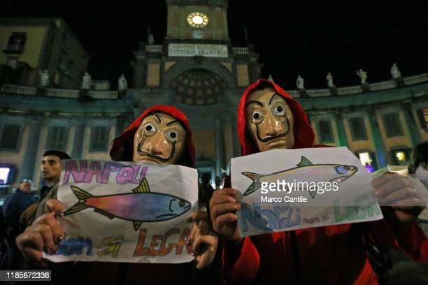Two persons, disguised as characters from the TV series Paper House, with placards showing a sardine during the Flash Mob, at Dante square in Naples,...