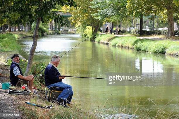 Two persons fish with their rods on August 27 on the banks of the Canal du Midi in Toulouse southwestern France AFP PHOTO REMY GABALDA
