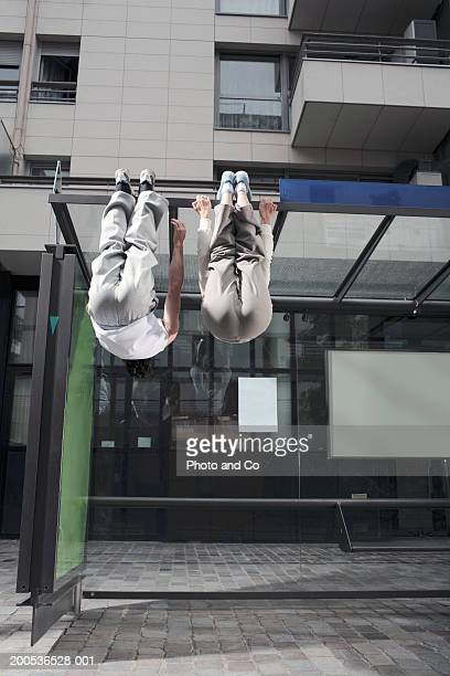 Two persons hanging from bus shelter, rear view