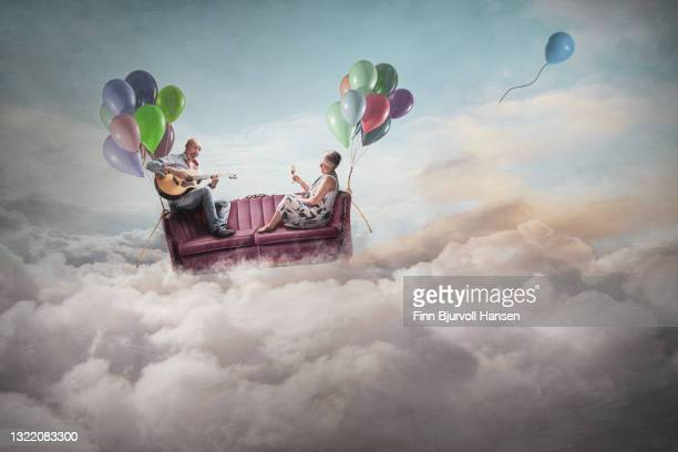 two persons in a sofa lifted by ballons flying above the clouds-fantasy image - finn bjurvoll foto e immagini stock