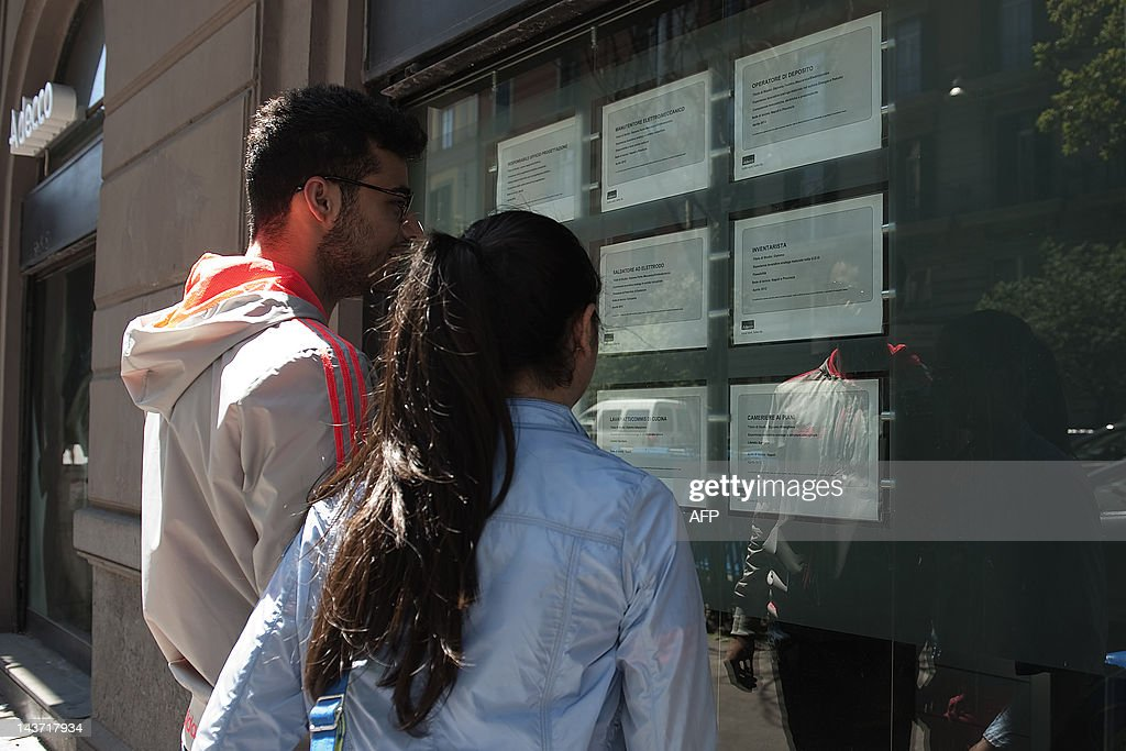 Two persons look at job announcements on : News Photo