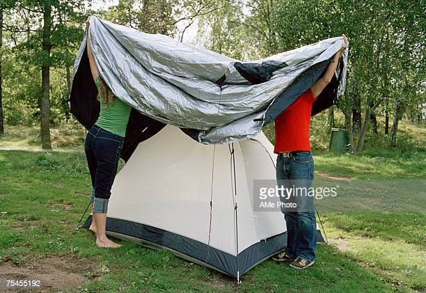 Two persons setting up a tent.