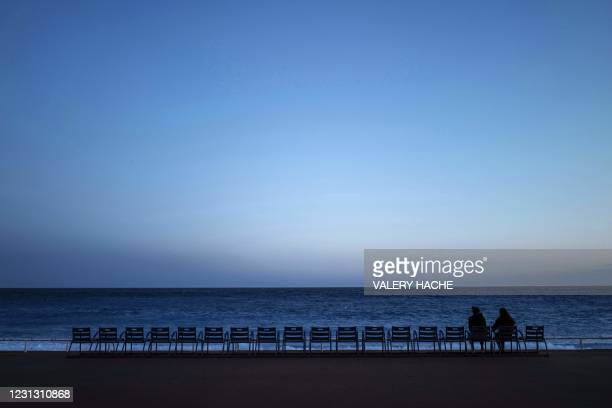 """Two persons sit in front of the Mediterranean Sea at early evening on the """"Promenade des Anglais"""" in the French riviera city of Nice, on February 21,..."""