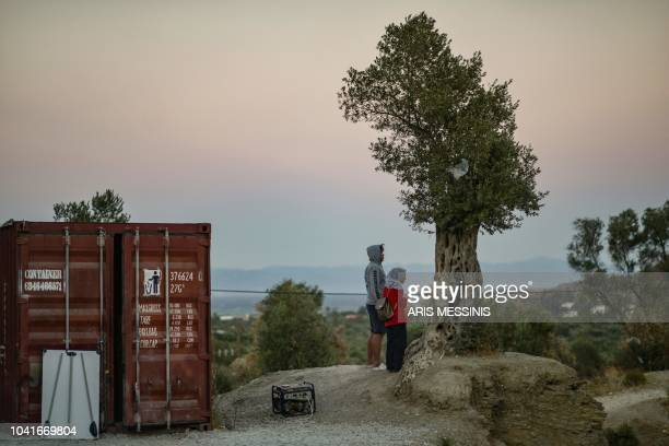 Two persons stand outside the refugee camp of Moria in the northern Greek island of Lesbos on September 25 2018 Despite a 2016 agreement between...