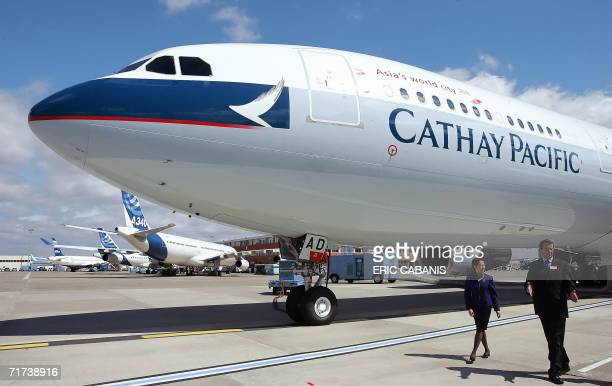 Two persons walk past an Airbus A330300 the 100th plane delivered to Cathay Pacific the Asian airline based in HongKong 29 August 2006 at...