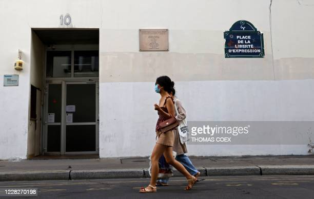 Two persons walk past the building where journalists of the Charlie Hebdo newspaper were killed by jihadist gunmen in January 2015, in Paris, on...