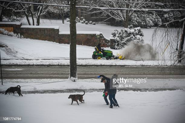 Two persons walk their dogs as a worker clears the snow in the background as snow continues to fall in Washington DC on January 13 2019 Washington...