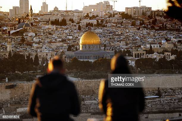 TOPSHOT Two persons watch the sun setting on the Old City of Jerusalem with the Muslim mosque of the Dome of the Rock in the center on January 23...