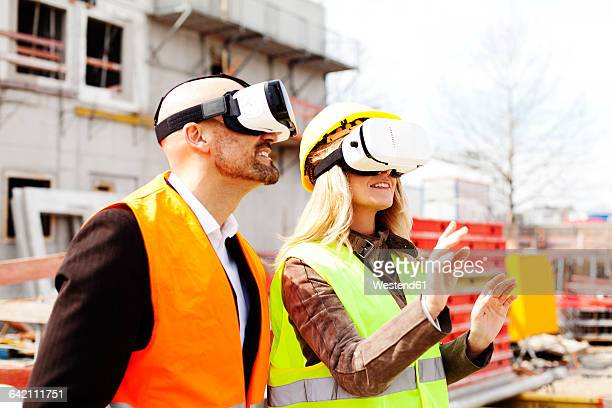 Two persons with Virtual Reality Glasses at construction site