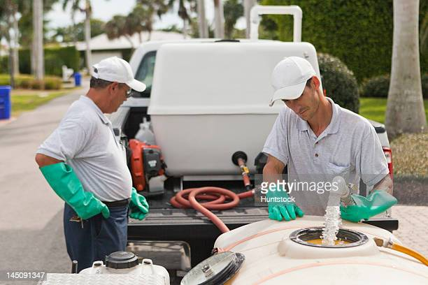 Two pest control technicians mixing chemicals in tank on service truck