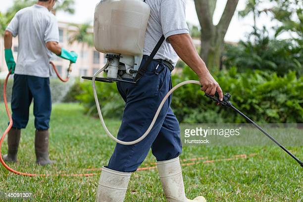 Two pest control technicians with portable spray rigs using spray guns