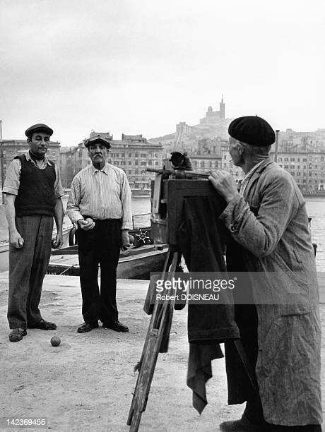 Two petanque players being pictured in front of Le Vieux Port Marseille France in 1951