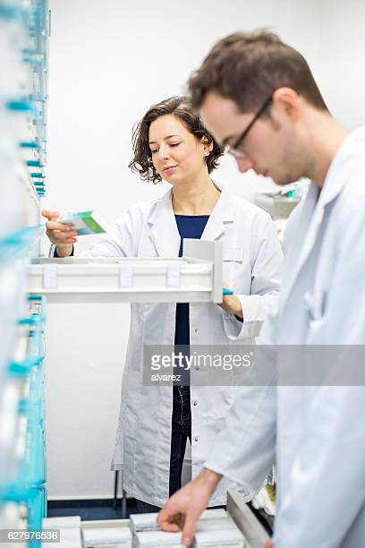 Two pharmacists looking for prescription medication