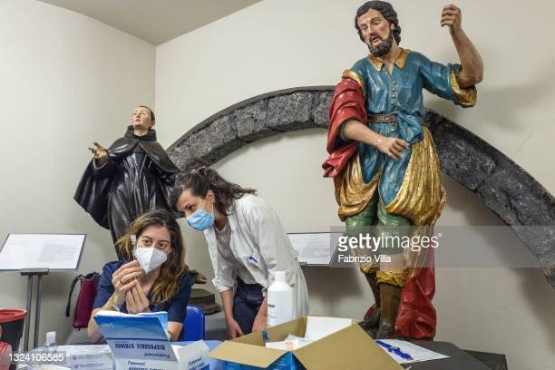 Two pharmacists prepare doses of the Covid vaccine before administering it in a room of the Diocesan Museum of Catania, amidst sacred statues on June...