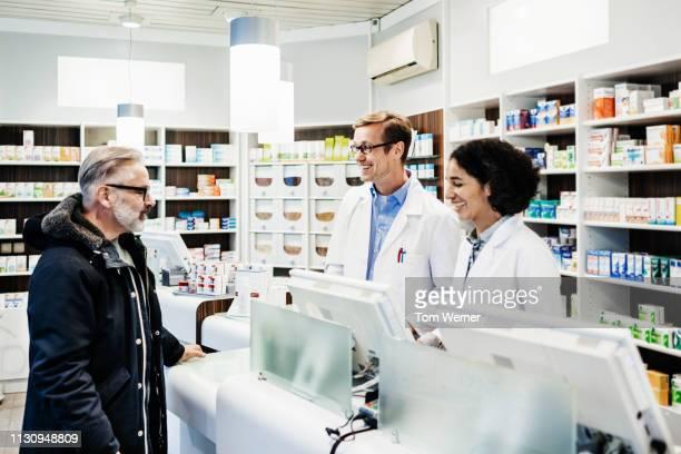 two pharmacists talking to customer - apotheke stock-fotos und bilder