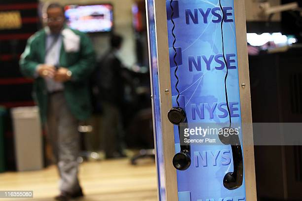 Two phone recievers hang as traders work on the floor of the New York Stock Exchange before the close on June 15 2011 in New York City Reversing much...