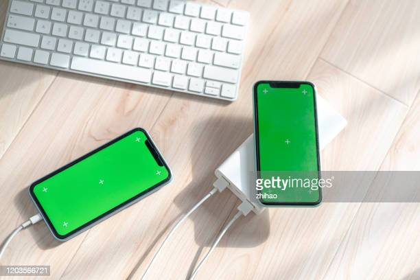 two phones are charging - two objects stock pictures, royalty-free photos & images