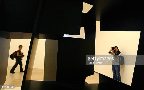 Two photographers are seen through Spanish Basque artist Jorge Oteiza's sculpture 'Retrato de un Gudari Armado llamado Odiseo' 07 October 2004 during...
