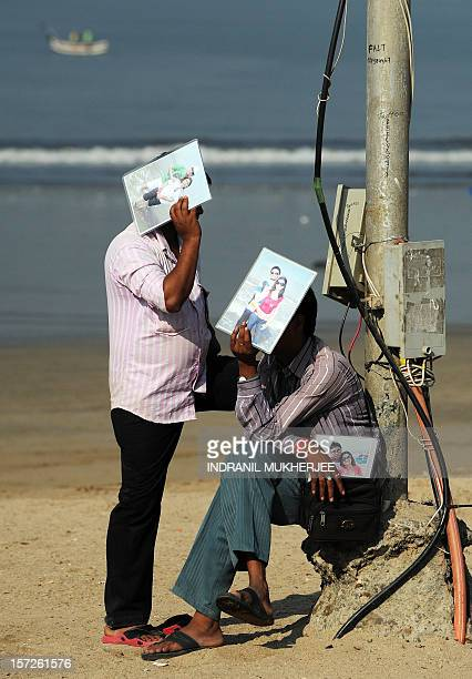 Two photographers chat while shielding their faces from the sun with photographs of tourist couples as they wait for customers at the city's iconic...