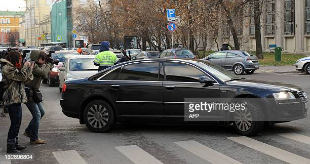 Two photographers follow the car of Moscow's toppled mayor Yuri Luzhkov near the police investigators' offices in downtown Moscow on November 15 2011...
