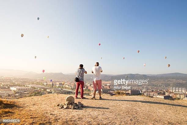Two photographers taking pictures of the European Balloon Festival meeting in the city of Igualada from elevated hill on the morning Catalonia Europe...