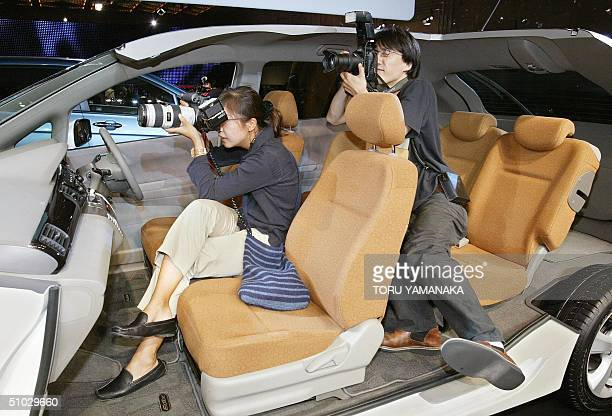 Two photographers try to take pictures of President of Japan's auto maker Honda Motor Takeo Fukui from a cutoff model of its new minivan Edix...