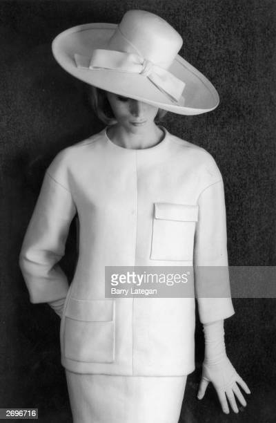 A two piece in heavy white linen designed by Yves St Laurent The box type jacket has bracelet length sleeves no collar patch pockets and a dropped...