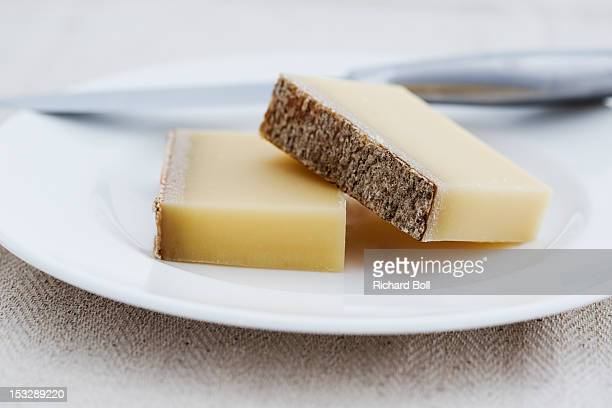 Two pieces of Gruyere cheese on a white plate