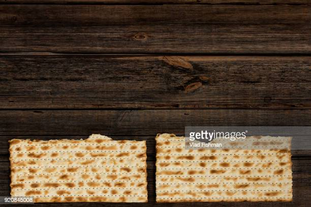 two pieces of matzah on a vintage wood background with copy space or text space. - happy passover stock pictures, royalty-free photos & images