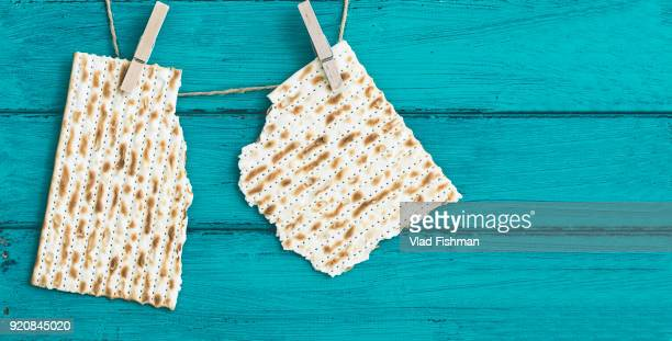 two pieces of matzah on a vintage wood background with copy space or text space. - passover symbols stock pictures, royalty-free photos & images