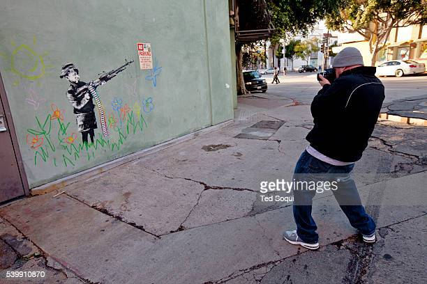 Two pieces of street art by Banksy appears in Los Angeles This one is a childlike wall drawing with flowers and a smiley sun with a black and white...