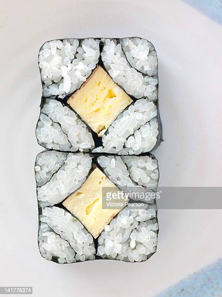 two pieces of tamago maki (egg sushi) on a plate. - maki sushi stock pictures, royalty-free photos & images