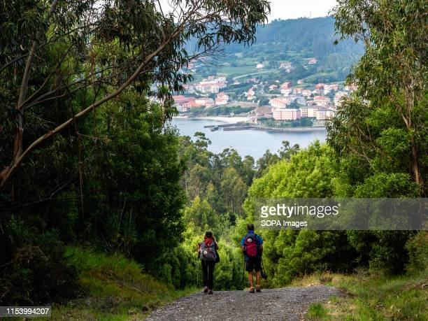 Two pilgrims are seen walking to Finisterra. Cape Finisterre is the destination of those pilgrims who, after visiting the St James tomb is Santiago,...