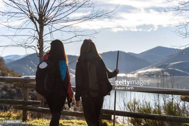 two pilgrims females looking at the landscape on the way to santiago de compostela - peregrino fotografías e imágenes de stock