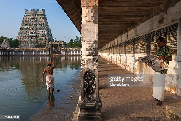 CONTENT] Two pilgrims one bathing and the other reading newspapers inside the Nataraja temple in Chidambaram Tamil Nadu India Thillai Natarajah...