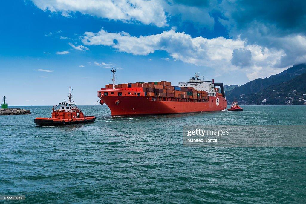 Two pilot ship take a cargo ship  inside the port : Stock Photo