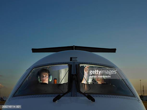 Two pilots in cockpit of plane, view through glass