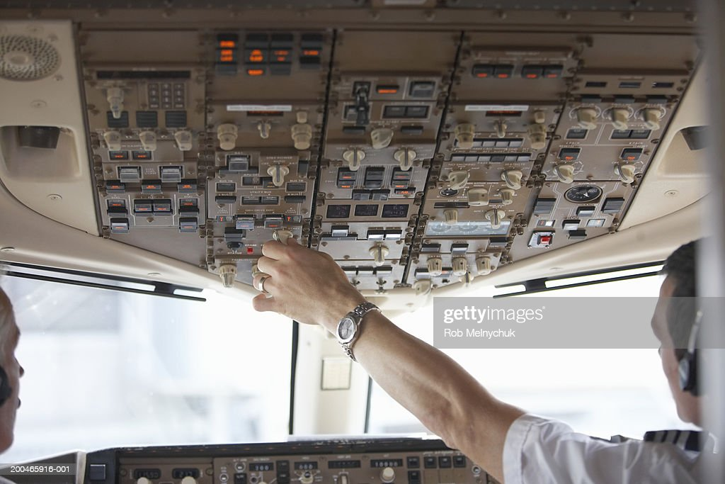 Two pilots in cockpit, one touching control panel, rear view : Stock Photo