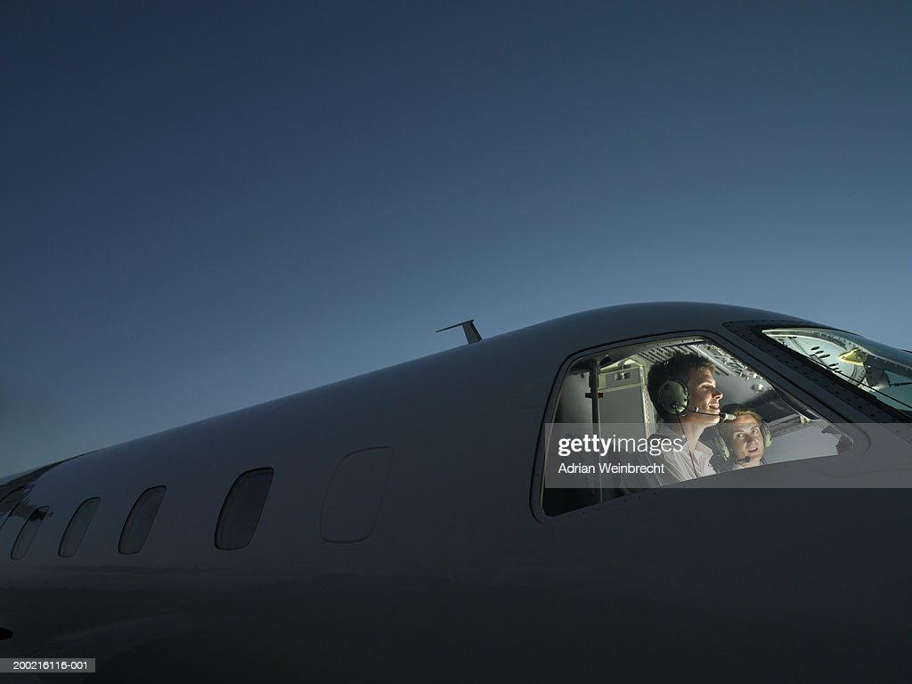 Two pilots in illuminated cockpit of plane, smiling : Stock Photo