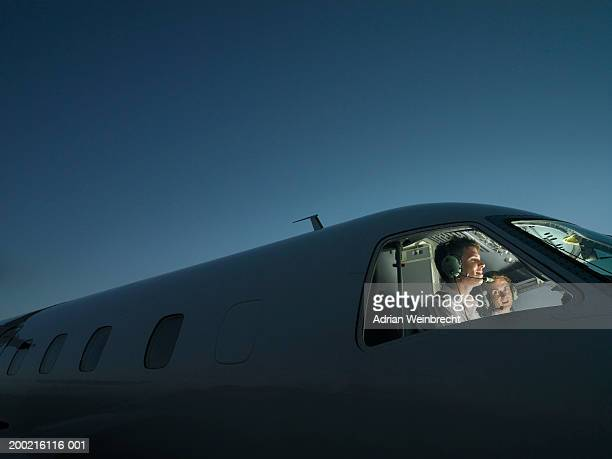 two pilots in illuminated cockpit of plane, smiling - piloting stock pictures, royalty-free photos & images