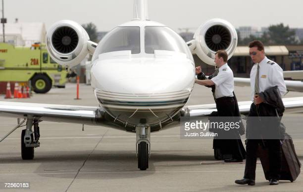 Two pilots walk away from a private jet at ACM Aviation March 9 2002 at San Jose Airport in San Jose CA Since the September 11 2001 terrorist attacks...