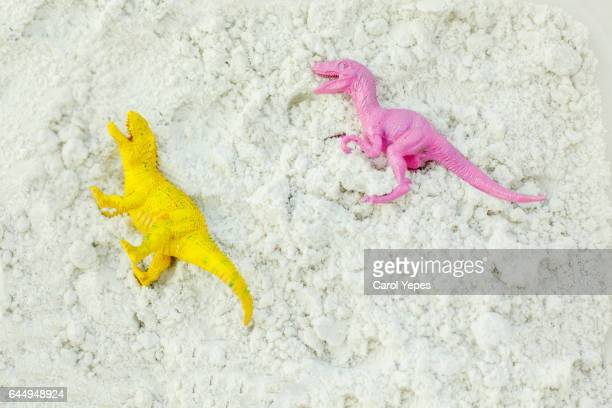 two pink and yello dinosaur  toys laying in sand