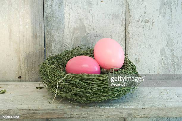 Two pink Easter eggs in an Easter nest