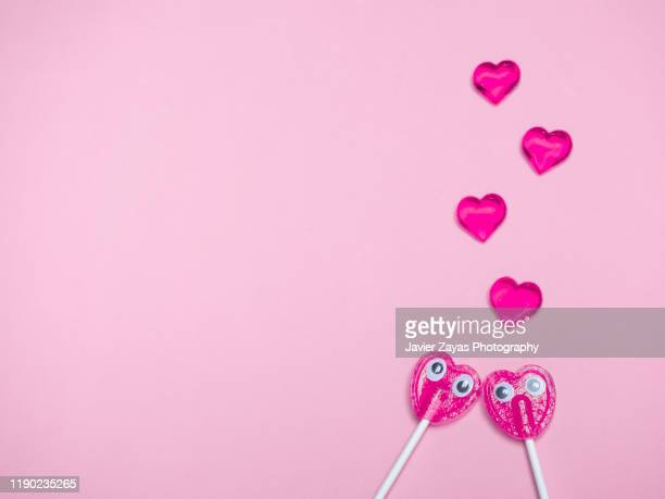 two pink heart lollipops with eyes falling in love in pink background - candy heart stock pictures, royalty-free photos & images