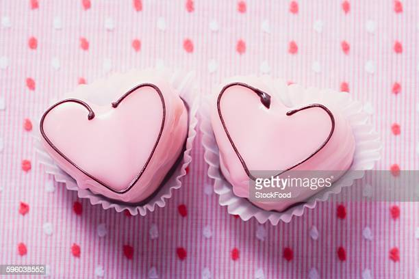 Two pink heart-shaped petit fours (overhead view)