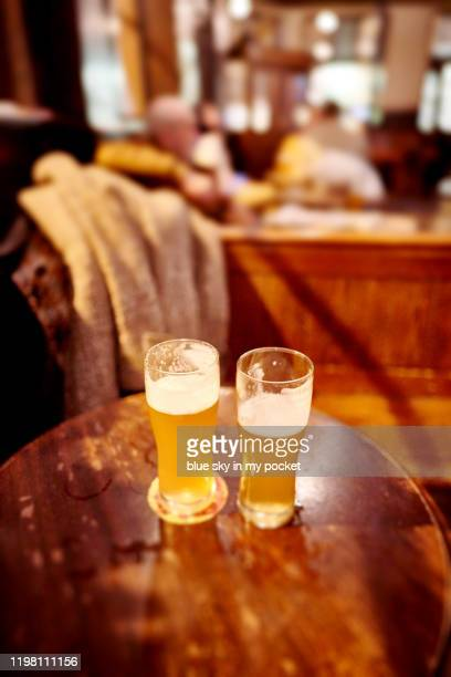 two pints of half full india pale ale - help:ipa stock pictures, royalty-free photos & images