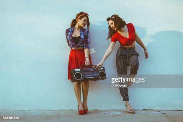 Two pin-up girls having fun and listening to music