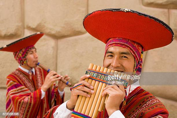 two pipers in traditional peruvian dresses - hugh sitton stock pictures, royalty-free photos & images