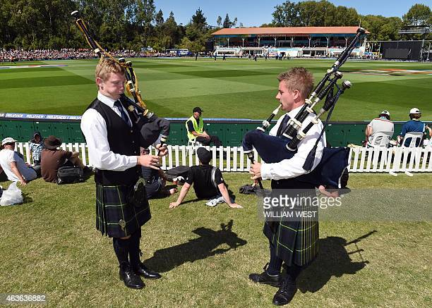 Two pipers play the bagpipes as New Zealand play Scotland during their 2015 Cricket World Cup match in Dunedin on February 17 2015 AFP PHOTO /...