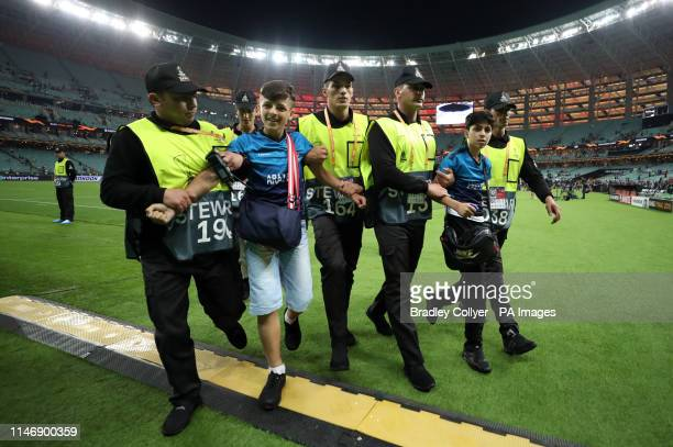 Two pitch invaders are escorted off during the UEFA Europa League final at The Olympic Stadium, Baku, Azerbaijan.